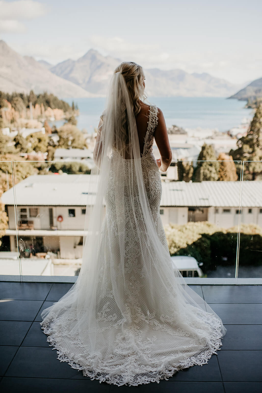 Stunning back of bride with detailed lace dress, looking out over Queenstown towards Walter Peak on one of our Queenstown Elopement Packages